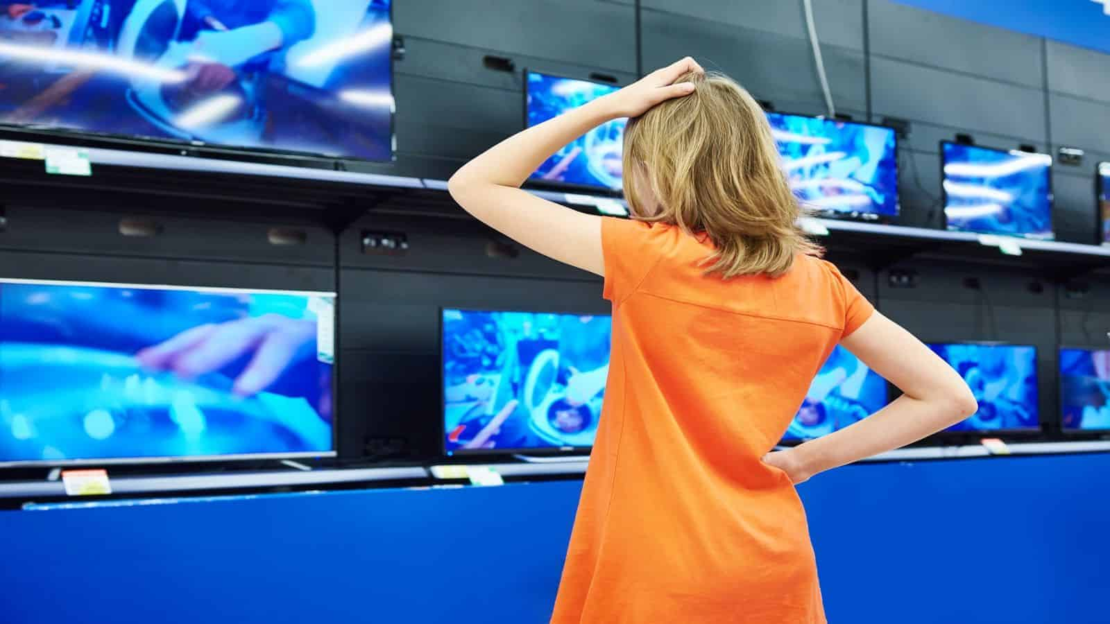 teenage girl looks at televisions TVs