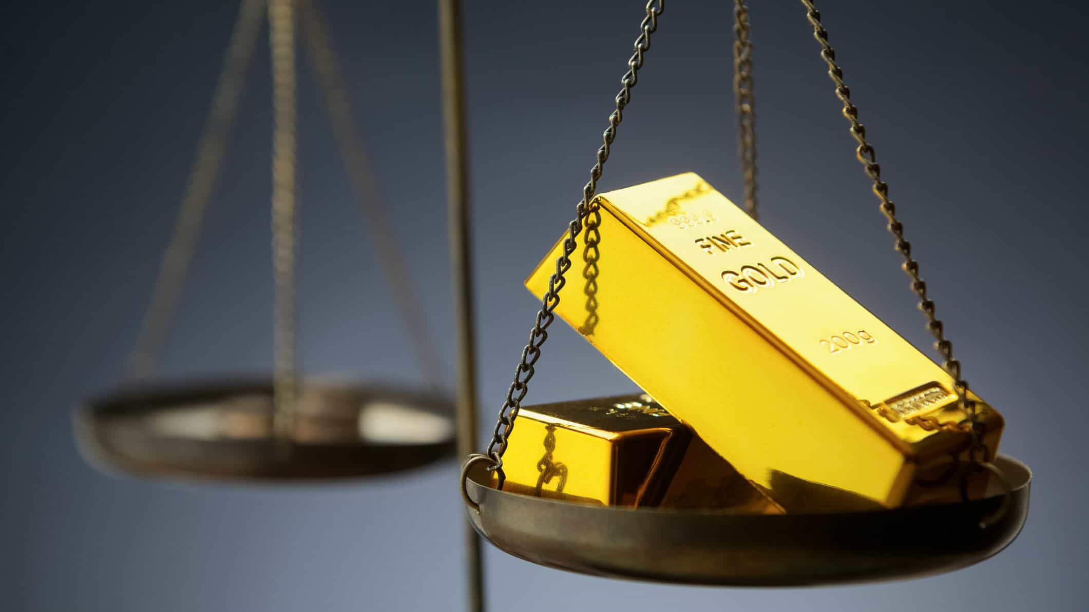Old fashioned scales weighing two gold bars in front of dark background, gold share price, newcrest mining share price