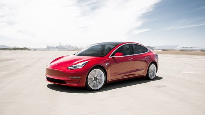 Red Tesla model 3 car on desert backdrop