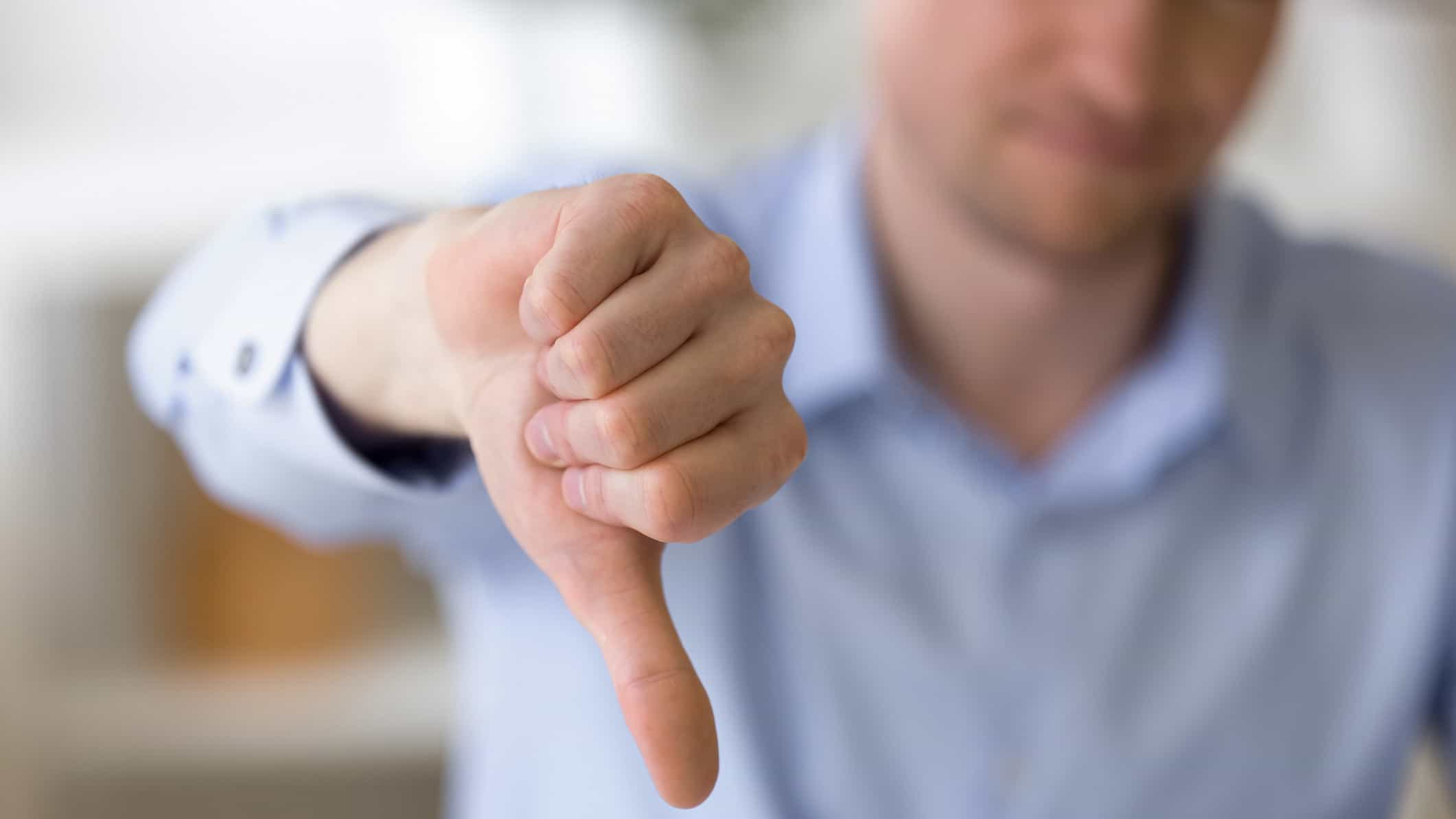 man making thumbs down gesture