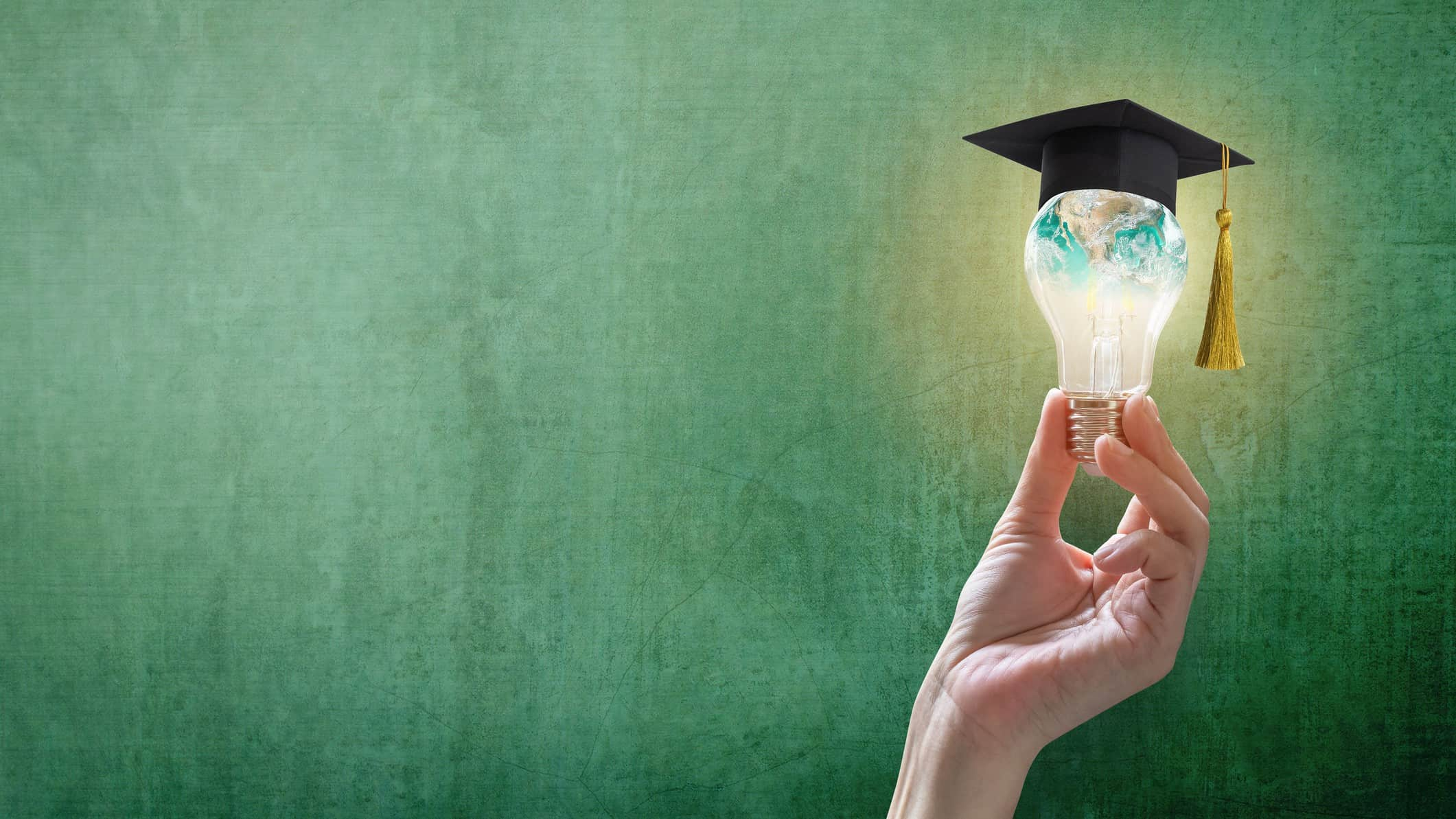 Hand holds up a lightbulb with a small graduates cap on top of it to symbolise wisdom and ideas